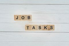 Top view of job tasks inscription made of wooden block on white. Wooden tabletop royalty free stock photos