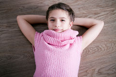Top view of a joyful young girl. Looking at something interesting while lying on the wooden floor - colorized photo Royalty Free Stock Image