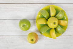 Top view of juicy yellow and green apples placed around the whole apple on a saucer. stock photos