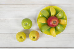 Top view of juicy yellow and green apples placed around the whole apple on a saucer. royalty free stock images