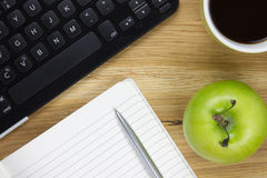Top-view of keyboard, apple and writing equipment. Top-view of a keyboard, green apple, coffee mug and writing equipment Stock Image