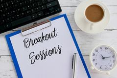 Top view of keyboard,coffee,clock,pen,clipboard and paper written with Breakout Sessions. Digital letters communication term motivational work black present stock image