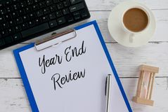 Top view of keyboard,coffee,sand clock,pen,clipboard and paper written with Year End Review. Analysis message creative marketing countdown change new goal royalty free stock image