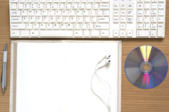 top view of keyboard computer notebook earphone and dvd disk Royalty Free Stock Image