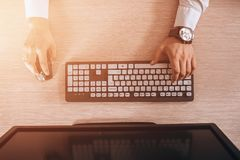 Top view of keyboard with men`s hands. Free black monitor copy space for design. Warm glare of sun light.  Royalty Free Stock Image