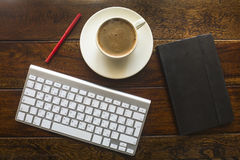 Top view of keyboard, pencil, black notebook and a cup of coffee on a wooden table. Royalty Free Stock Photo