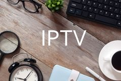 Top view of keyboard,plant,sunglasses,a cup of coffee,pen,notebook,clock and magnifying glass on wooden floor written with IPTV