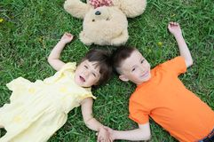 Top view of kids lying on the grass at park having fun. Little girl and boy relax with smiling. Teddy bear toy royalty free stock photo