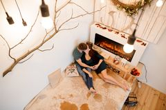 Top view of kissing pregnant couple lying near the burning fireplace Stock Images