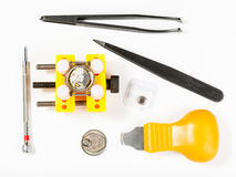 Top view of kit for replacing battery in watch. Watchmaker workshop - top view of kit for replacing battery in watch on white background Royalty Free Stock Image