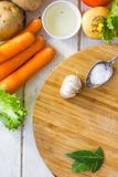 Top view of kitchen scene - bay leaves and some vegetables over wooden board. Stock Photography