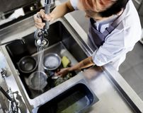 Top view of kitchen staff washing utensils at sink stock photos