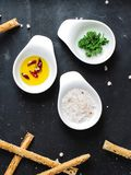 Top view of three sauce boats with rose salt, oil with spices and leaves of fresh parsley stock photos