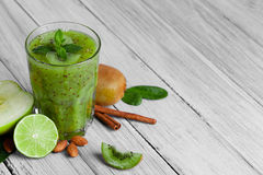 A top view of a kiwi smoothie with mint on a wooden background. Tropical fruits, cinnamon, lime and apple near a drink. Stock Image