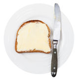 Top view of knife and bread and butter on plate Royalty Free Stock Photography