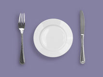 Top view of knife, plate and fork on violet Stock Photography
