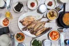 Grilled fish served in white dish during dinner time. A top view of korean foods during dinner time. Grilled fish are nice to eat . Jks stock photos