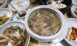 A Korean mushroom soup is served with other Korean dishes. A top view of a korean mushroom soup with other korean side dishes stock photos