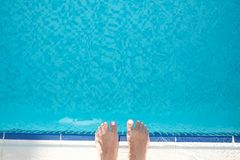 The top view on the ladies feet near the beautiful blue pool royalty free stock photo