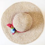 Top view of ladies` wide brim straw hat on white. Top view of ladies` wide brim straw hat with red band and textile flower on white background Stock Photos