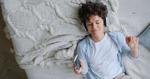 Top view of lady listening to music in bed through headphones using smartphone. Top view of young lady listening to music through headphones in bed with closed stock footage