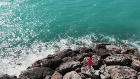 Top view of lady woman in red dress standing on rocky pier or cliff with hands apart in air looking at blue sea and sky with sun r. Eflection on water. Coral Bay stock footage