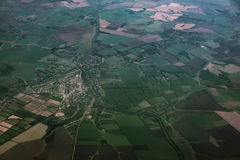 Top view of land, green fields with roads, view from airplane window Stock Photos