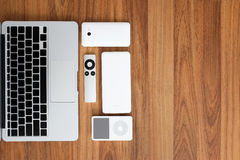 Top view of laptop computer with smartphone, remote, mouse, speaker, portable music player, battery pack. On wood top. Stock Photo