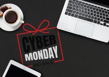Top view of laptop and cup of tea with cyber monday lettering on black background