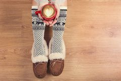 Top view of laptop in girl`s hands sitting on a wooden floor with cup of coffee, christmas decoration, gifts and wrapping paper stock photos