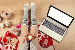 Top view of laptop in girl`s hands sitting on a wooden floor with cup of coffee, christmas decoration, gifts and wrapping paper royalty free stock photography