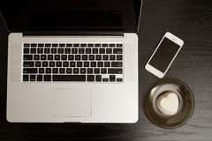 Top view of a laptop keyboard, smartphone and dessert on a black wooden table.  Royalty Free Stock Photos