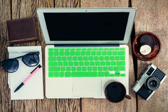 Top view of laptop, old camera, coffee cup, wallet, glasses, pen Royalty Free Stock Photo
