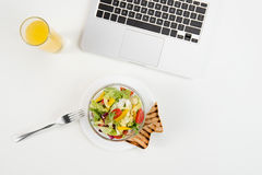 Top view of laptop, orange juice in glass and fresh healthy salad Stock Photos