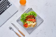Top view of laptop, orange juice in glass and fresh salad in lunch box at workplace.  royalty free stock image