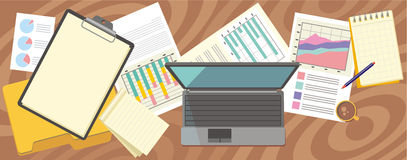 Top view laptop, papers with numbers and charts Royalty Free Stock Images
