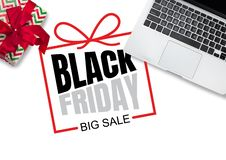 Top view of laptop and present, gift with black friday lettering on white background