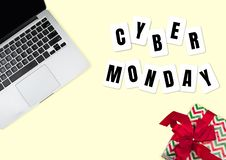 Top view of laptop and present, gift with cyber monday lettering on yellow background