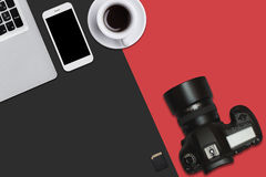 Top view of laptop, smart phone, flash card, camera and cup of coffee lying on red and black surface. Workplace of talented photog. Rapher with modern supplies Royalty Free Stock Photo