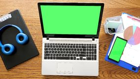 Top view laptop an smartphone with chroma green screen on a table stock video footage