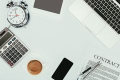 Top view of laptop, smartphone, contract with pens, alarm clock and calculator. On white royalty free stock photos