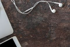 Top view laptop, smartphone and earphone on old wooden background with copy space. stock image