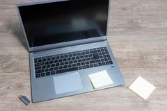 Top view of a laptop on a wooden table. With usb stick and paper royalty free stock images