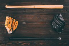 top view of leather baseball gloves and bats