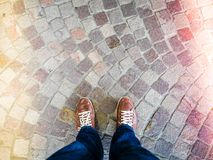 Top view of leather shoes on stone mosaic floor, colored light leaks coming from both sides.  stock images
