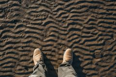 Top view of legs and beige suede boots standing on the beach. Stock Photography