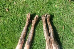Naked dirty legs on the grass. Top view legs of pretty young woman relaxing on grass Royalty Free Stock Photos