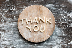 Top view of lettering thank you made from cookie dough with flour. On wooden cutting board royalty free stock image