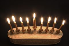 Top view of a lighted Hanukkah menorah against a black background. Horizontal aspect, space for text Stock Photo
