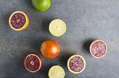 Top view of lime and blood juice.Slices and halves of exotic fruits on grey surface royalty free stock photography